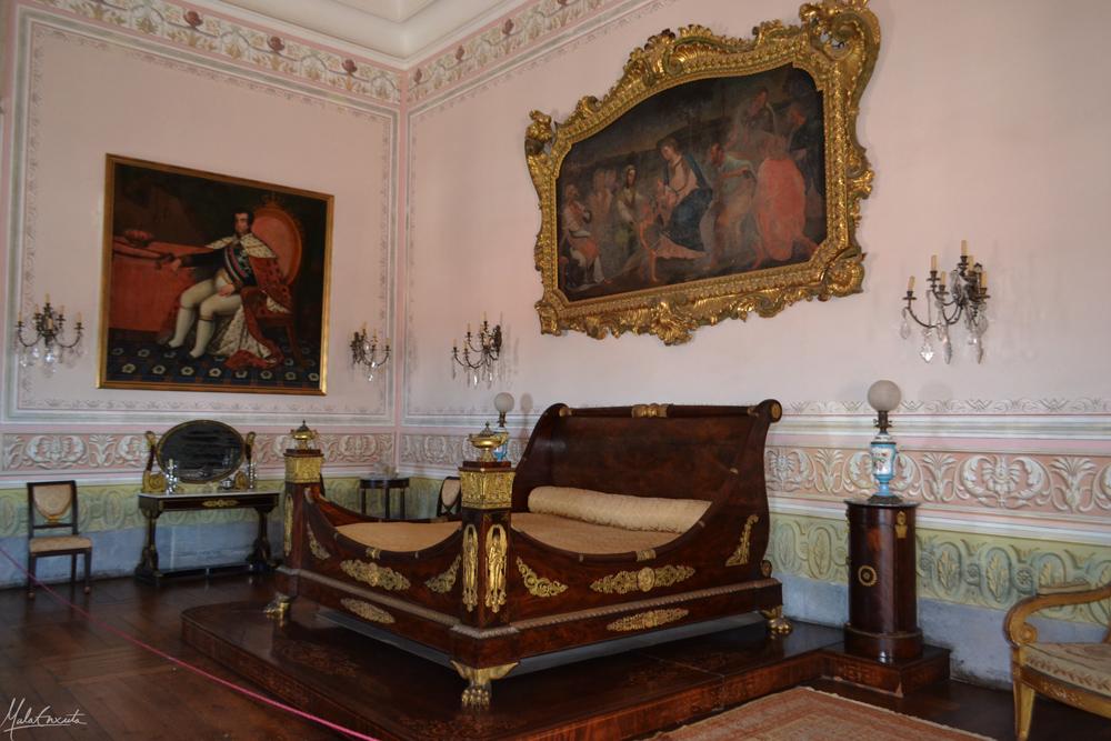 Quarto da Sua Majestade- à esquerda pintura de D. João VI e em cima da cama, da Sagrada Família.